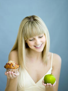 sensible eating, woman with cupcake and apple