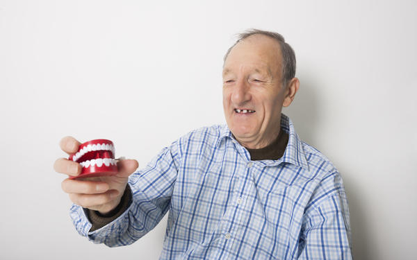 Happy man holding dentures
